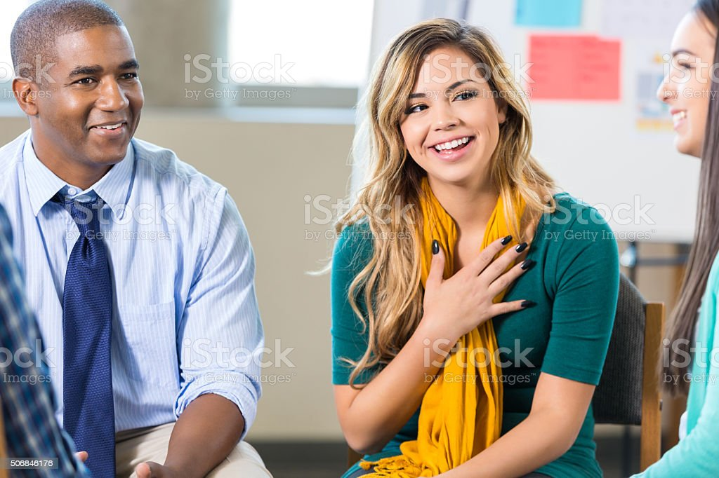 Young Hispanic woman participates in support group stock photo