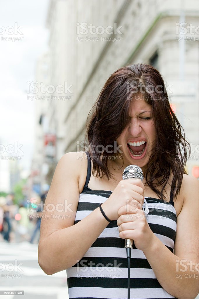 Young Hispanic woman singing into microphone in downtown city stock photo