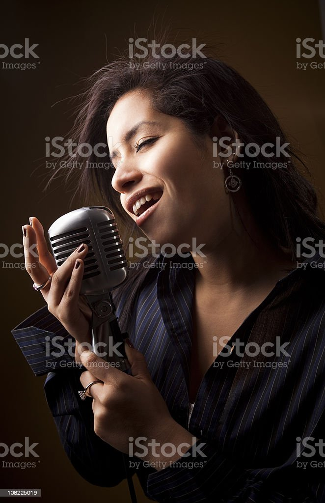 Young Hispanic Woman Singing into Retro Microphone royalty-free stock photo