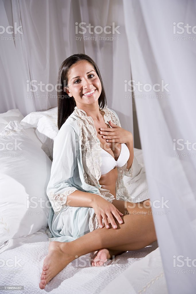 Young Hispanic woman sitting on white canopy bed royalty-free stock photo
