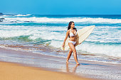 Young Hispanic Woman Walking on Hawaiian Beach with Surfboard
