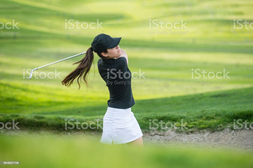 Young Hispanic Women Hitting The Ball Out Of A Bunker stock photo