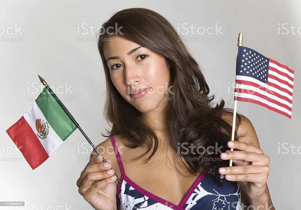 Young Hispanic women holds small Mexican and American flags stock photo