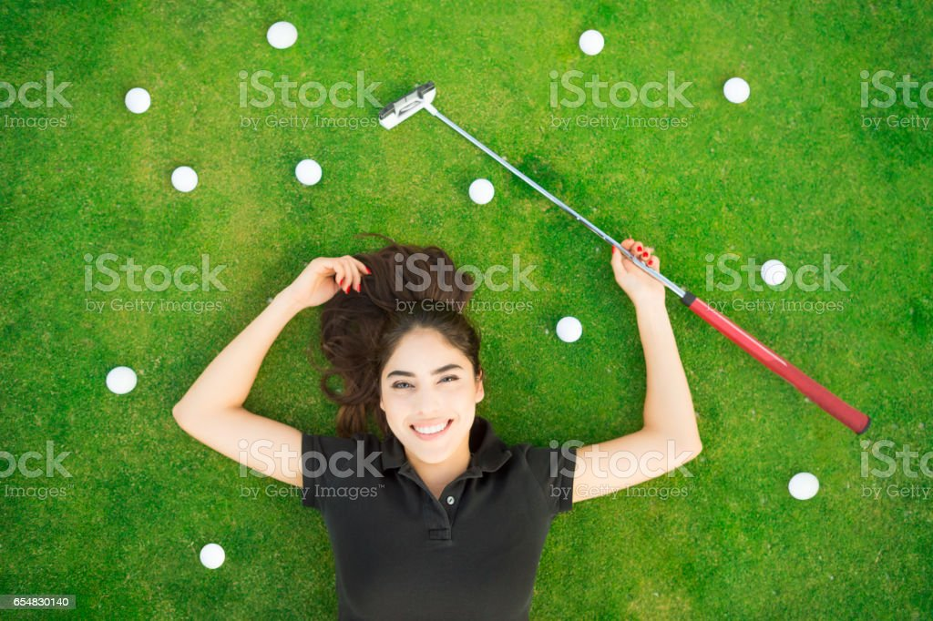 A young Hispanic women Laying on the putting green with golf balss...