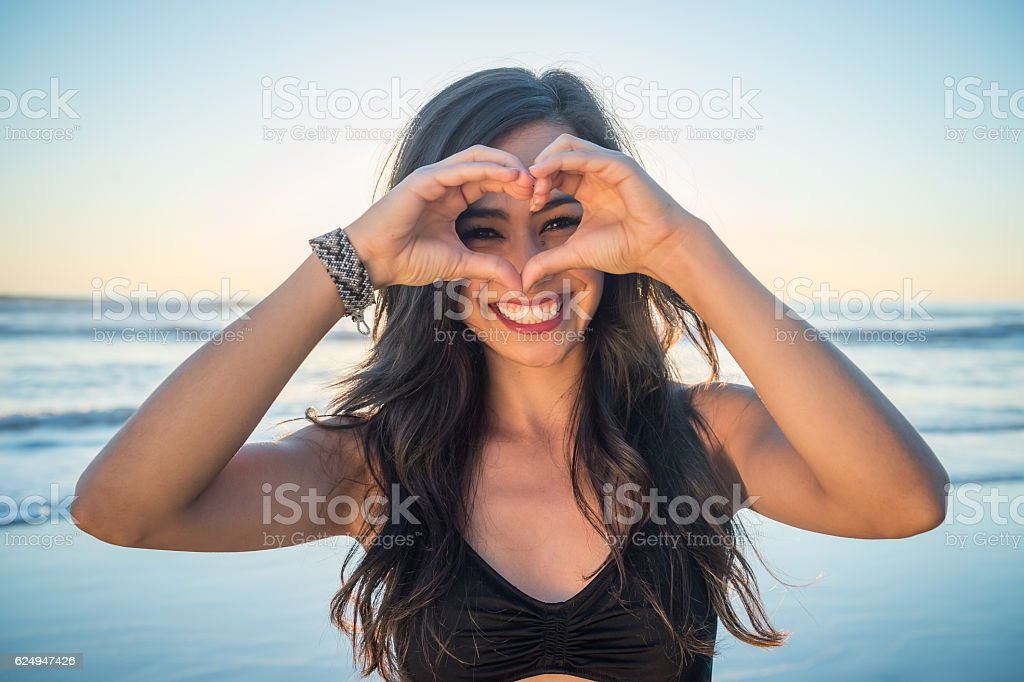 Young Hispanic Women On The Beach Heart Sign stock photo