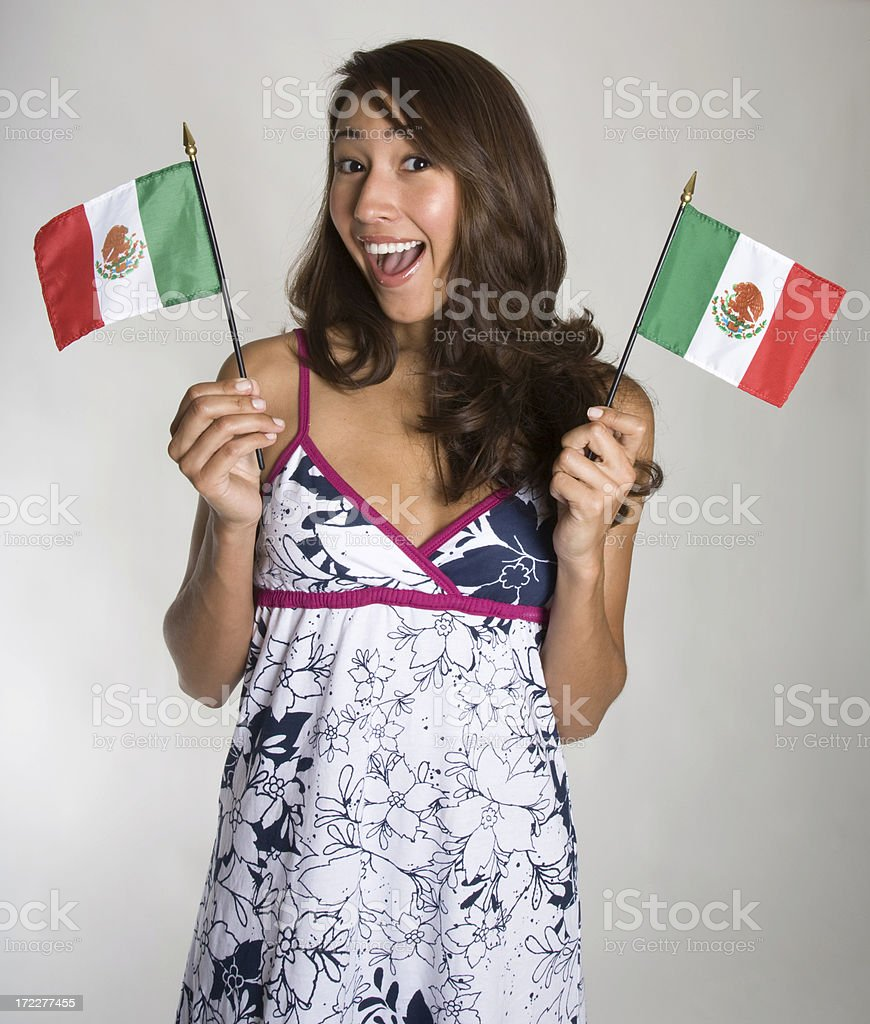 Young Hispanic women waves two small Mexican flags royalty-free stock photo