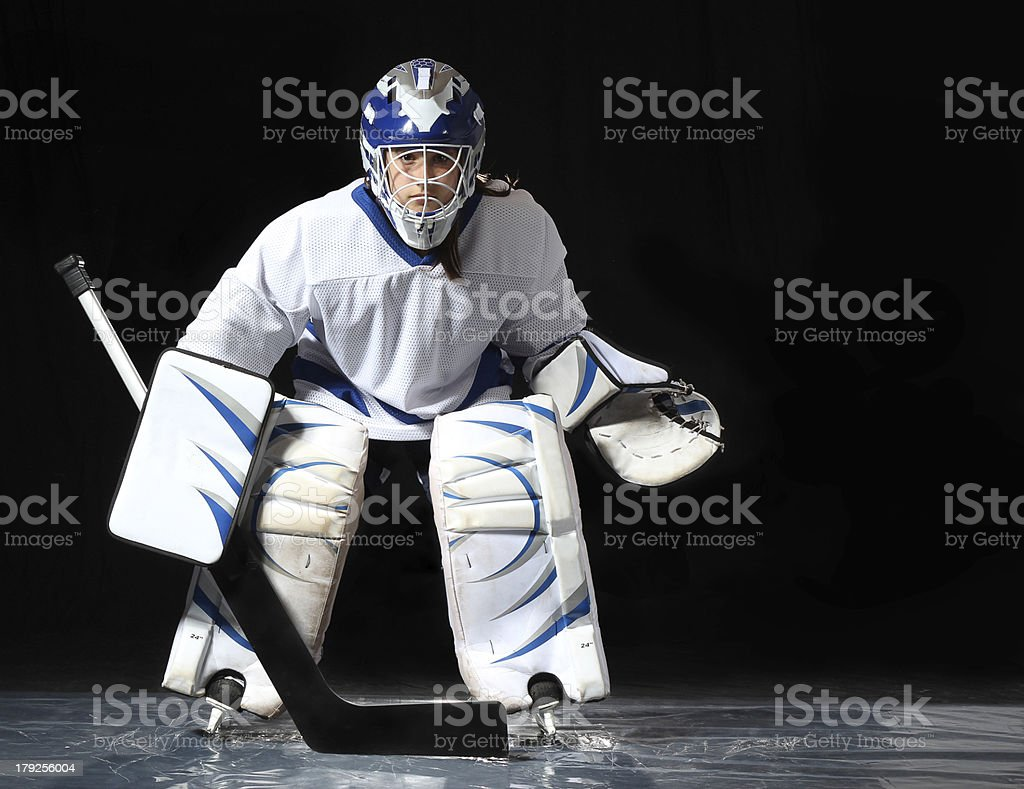 Young hockey goalie on a dark background stock photo