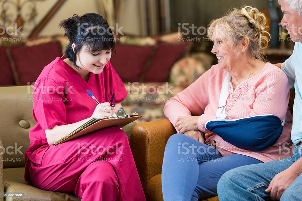 Young home healthcare nurse takes notes during home visit stock photo