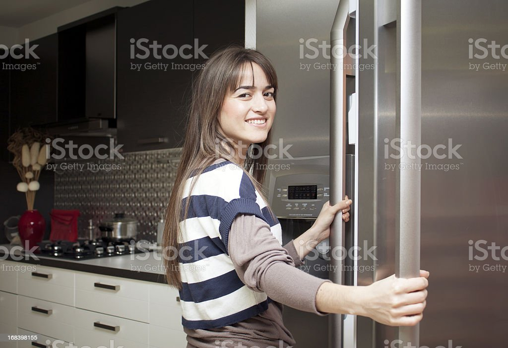 Young home maker checks the contents of her refrigerator, royalty-free stock photo