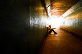 Young homeless adult male sitting and begging in subway tunnel