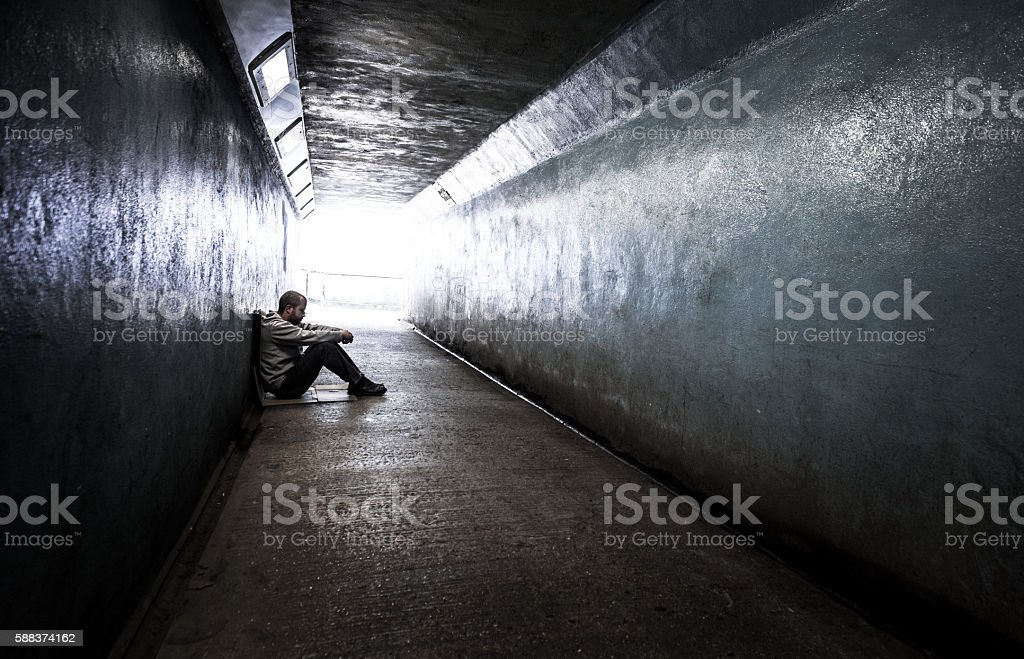 Young homeless adult male sitting in subway tunnel stock photo
