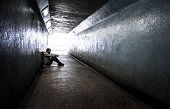 Young homeless adult male sitting in subway tunnel