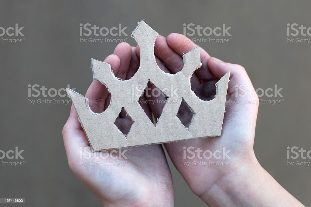 young homeless boy holds a cardboard crown stock photo