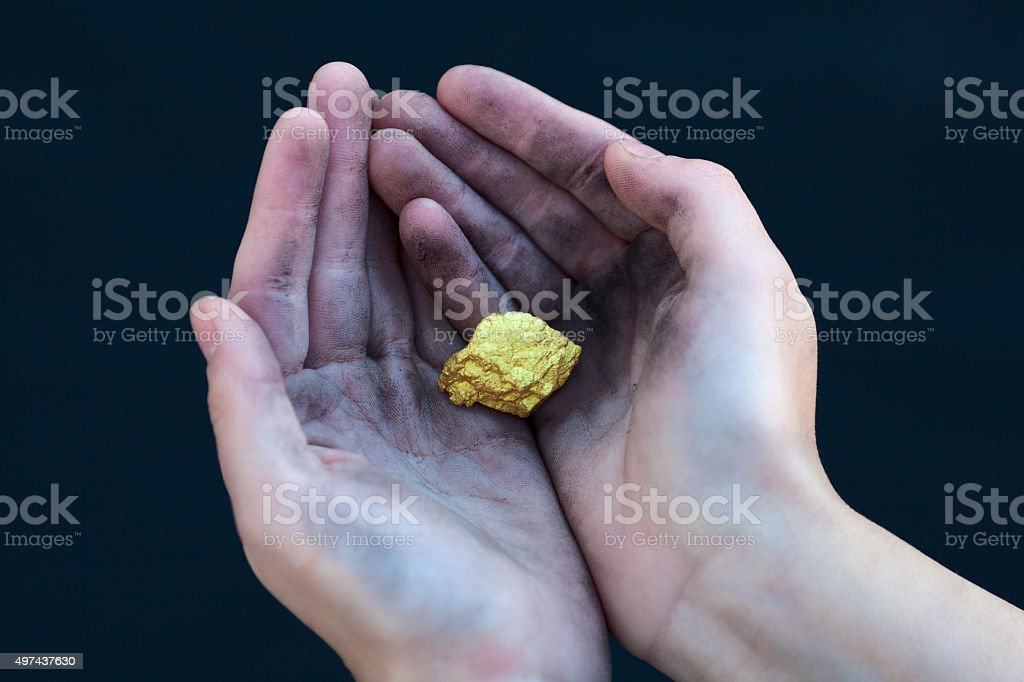 young homeless boy holds big gold nugget stock photo