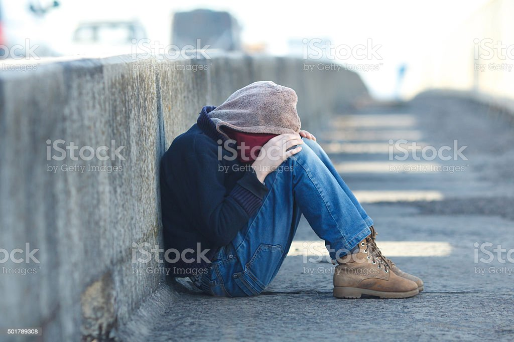 young homeless boy sleeping on the bridge stock photo