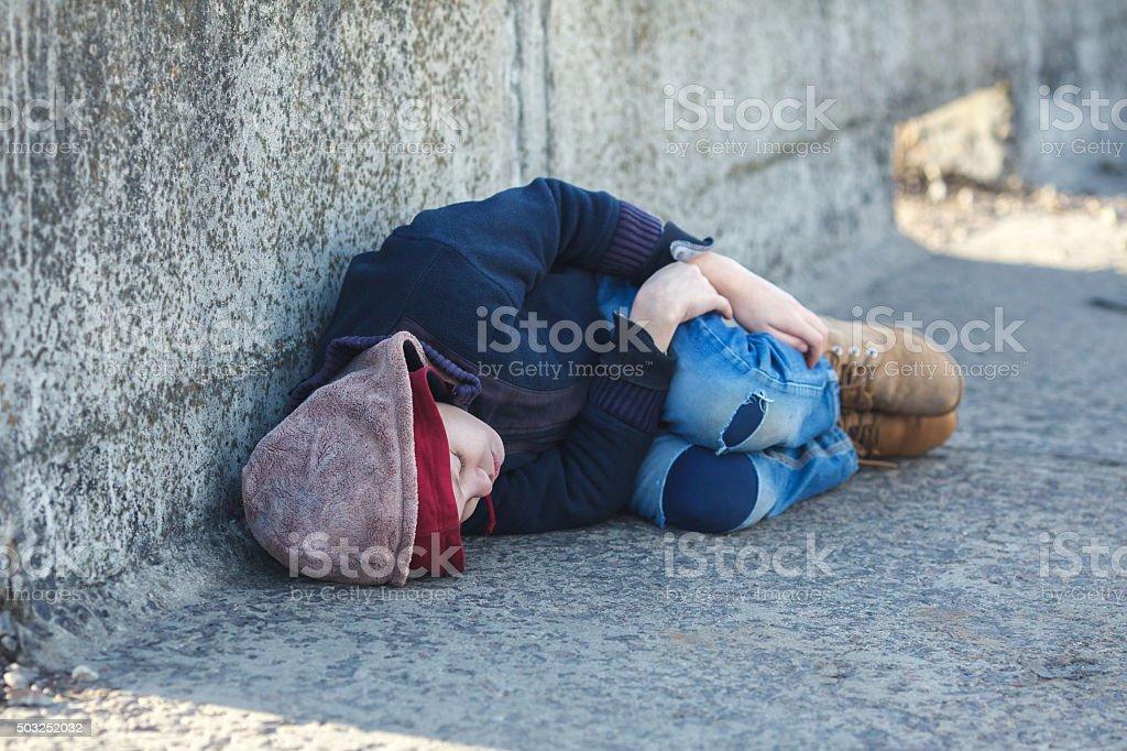 young homeless boy sleeping on the bridge stock photo