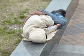 young homeless man sleeping on the street