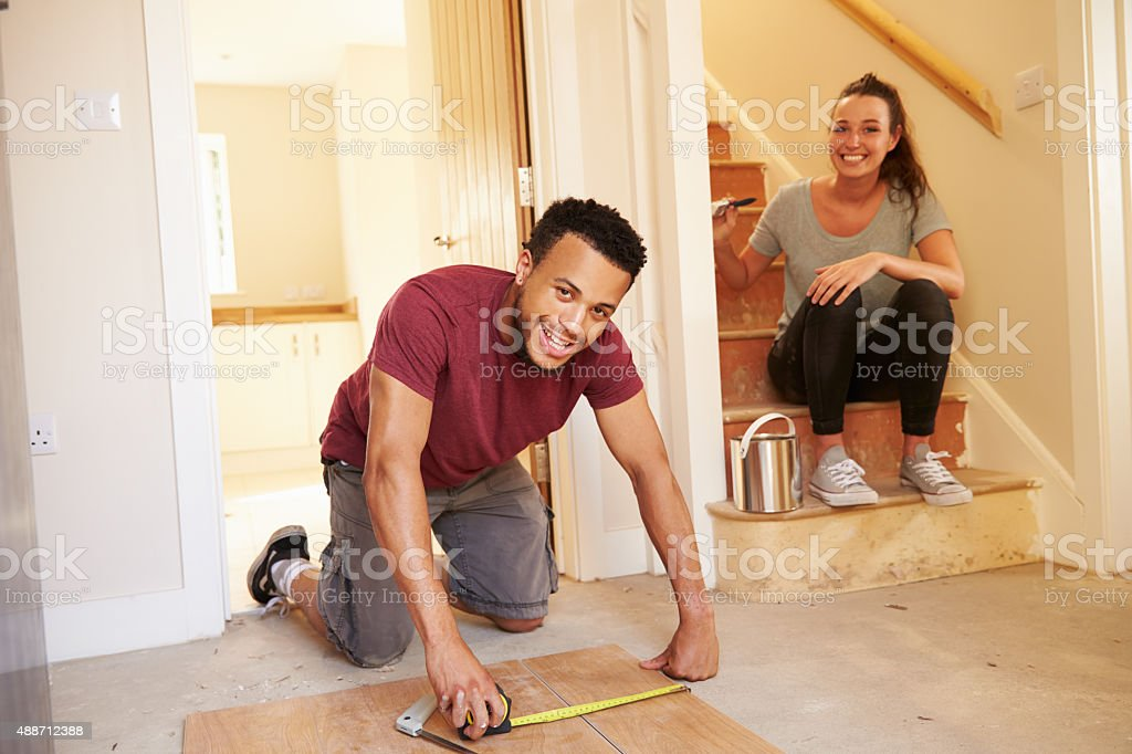 Young homeowners decorating their house, looking to camera stock photo