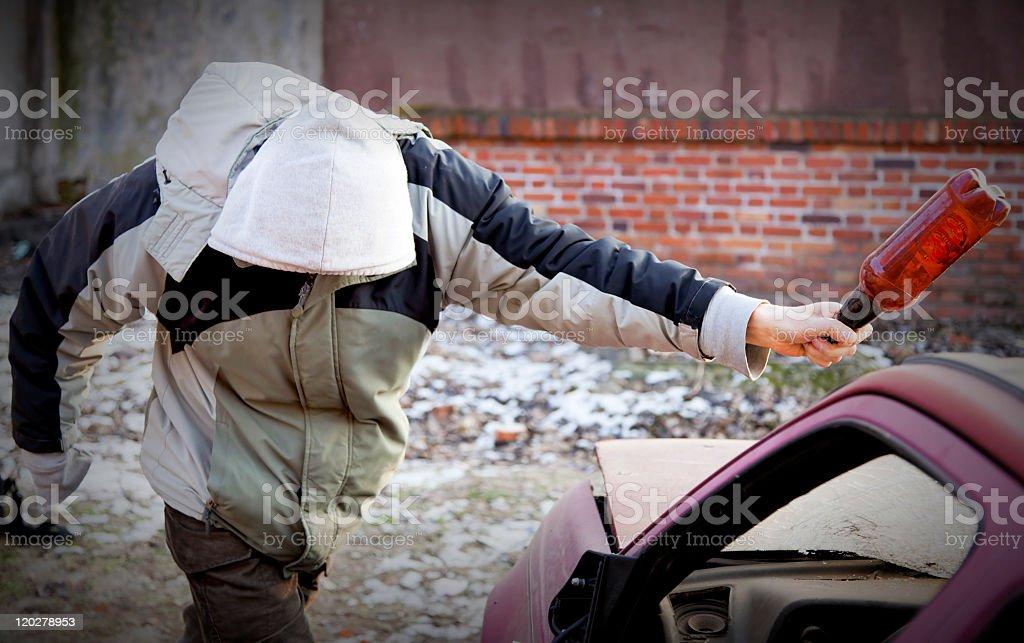 Young hooligan smashing windshield royalty-free stock photo