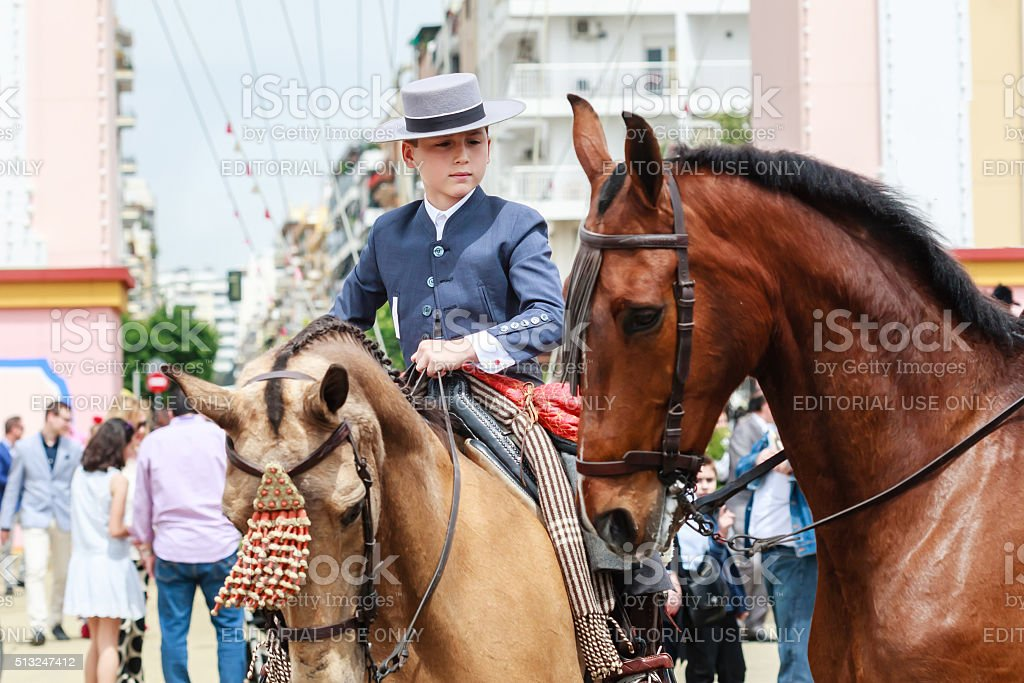 Young horse rider taking a walk at fair of Seville stock photo