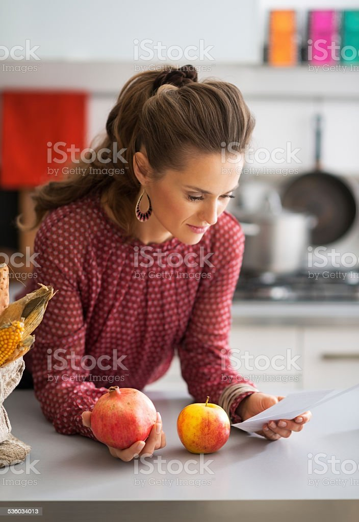 young housewife exploring checks after grocery shopping in kitchen stock photo