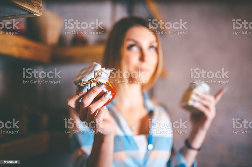 young housewife holding jars with homemade conserved food stock photo