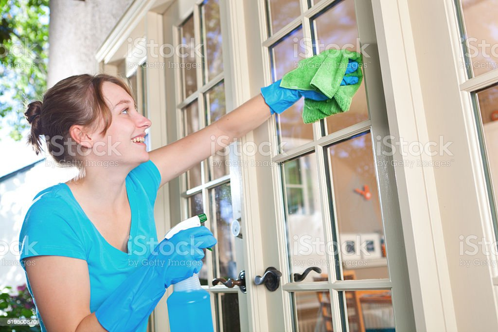 Young Housewife Spring Cleaning Windows Close-up stock photo