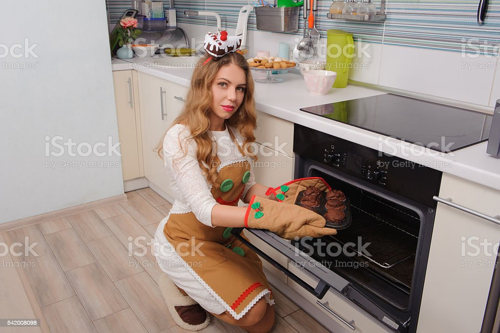 young housewife taking cupcakes from oven stock photo