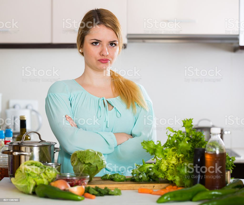 Young housewife tired of cooking vegetables in domestic kitchen stock photo
