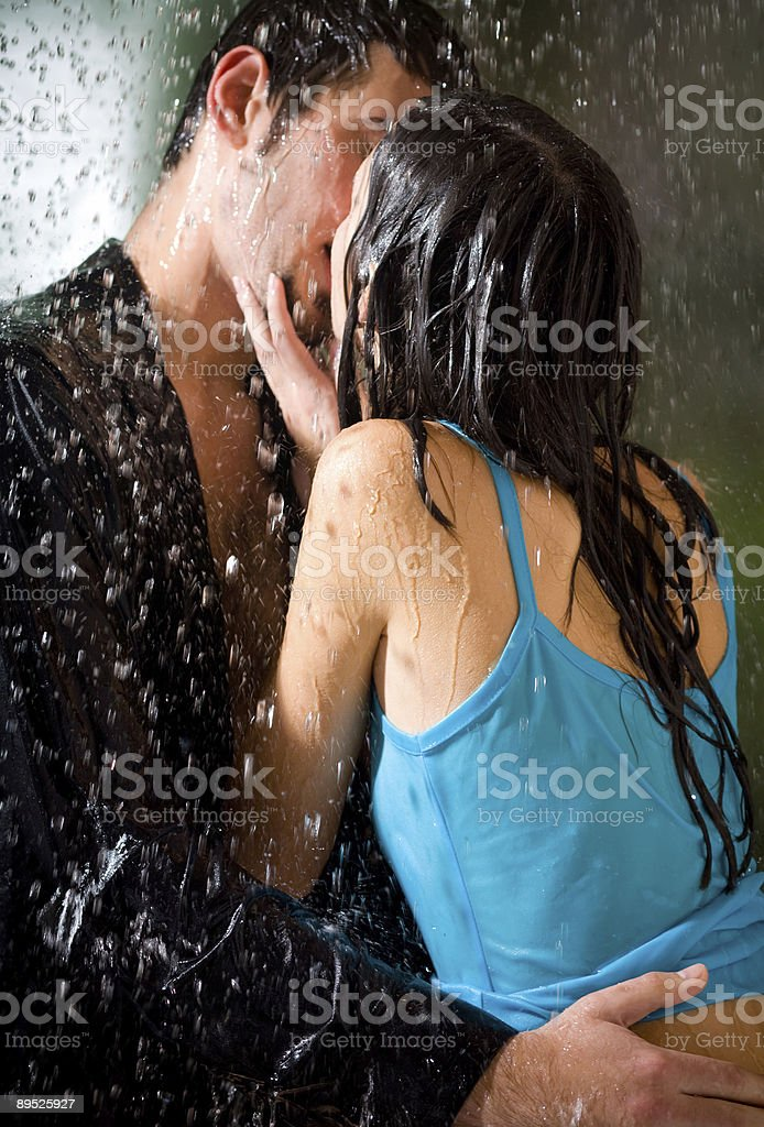 Young hugging couple kissing under a rain, in passion stock photo