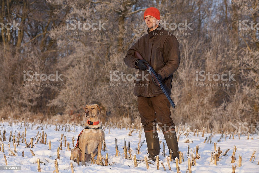 Young hunter with dog at winter hunting stock photo