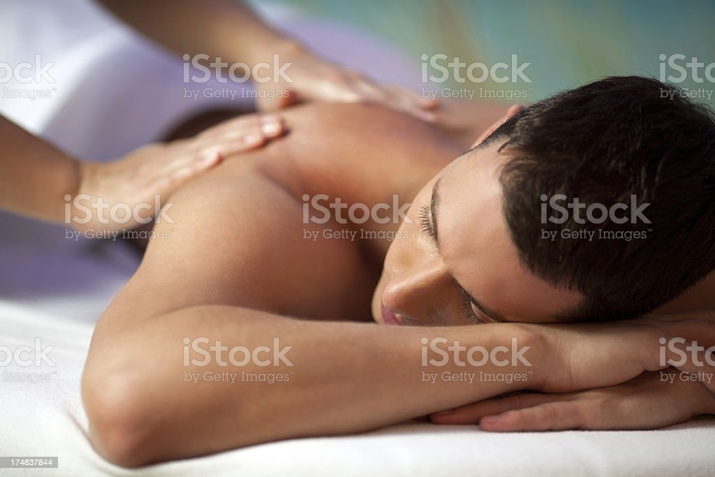 Young hyandsome man receiving back massage stock photo