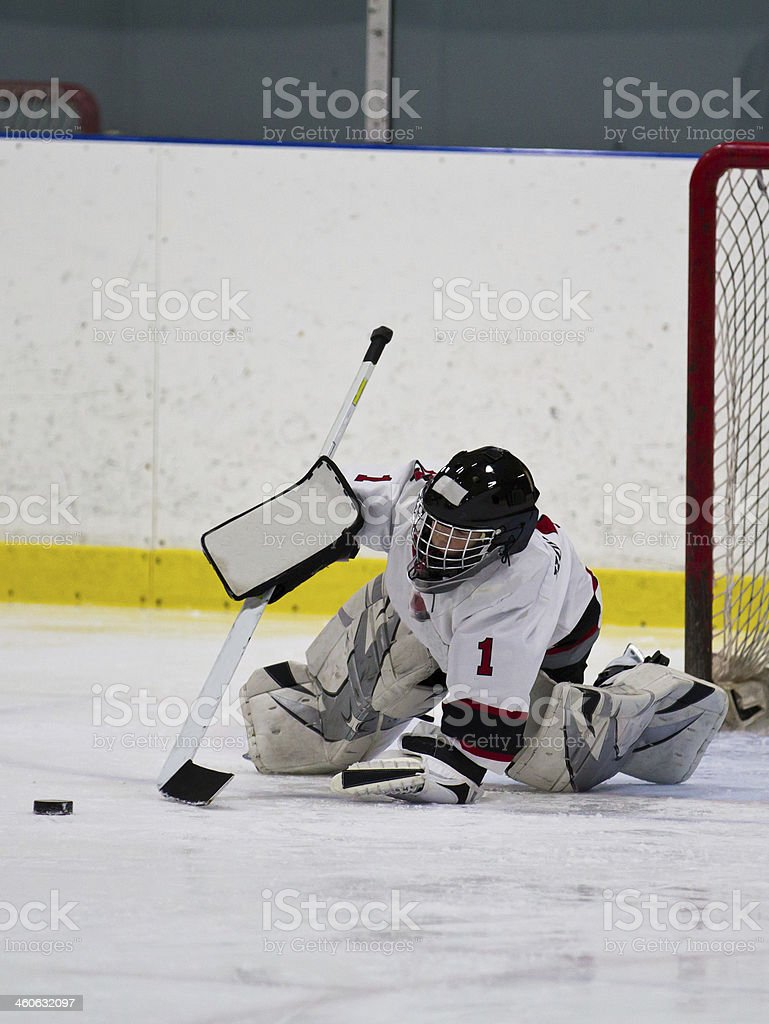 Young ice hockey goaltender making a save stock photo