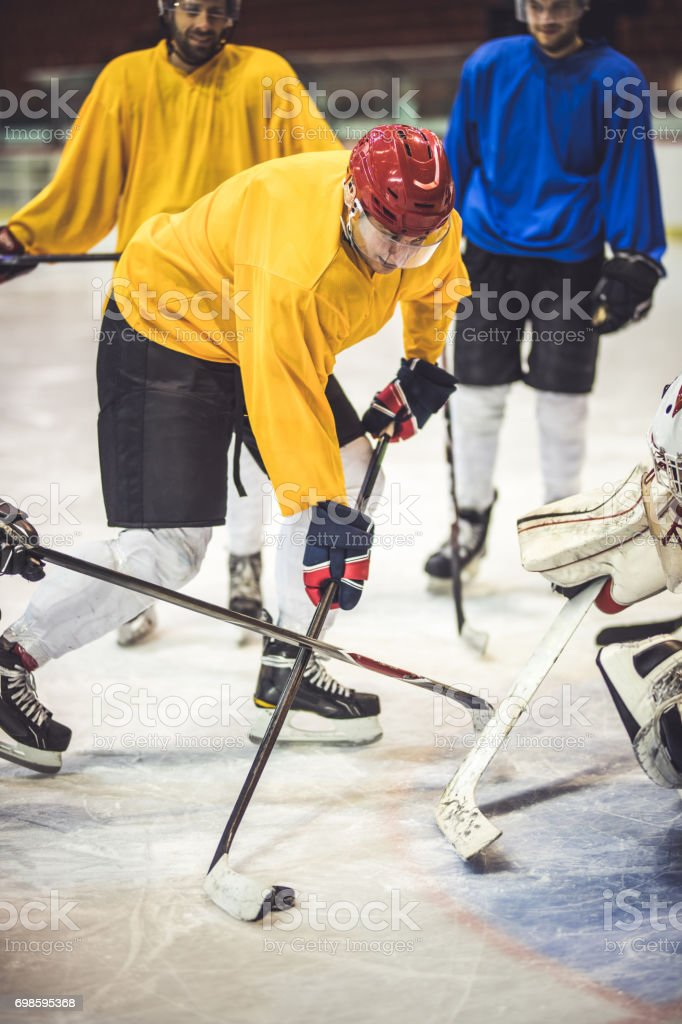 Young ice hockey player tackling his opponents during a match in a rink. stock photo