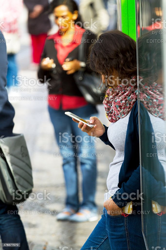 Young immigrant with mobile at bus stop in Oberhausen stock photo
