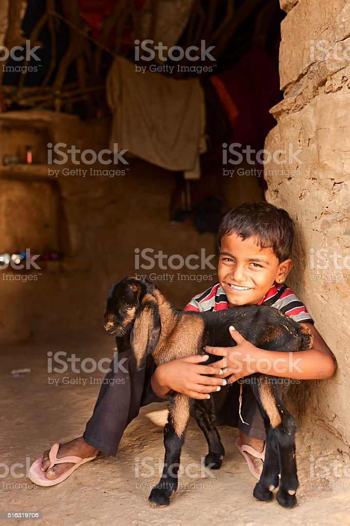 Young Indian boy holding a goat in village on desert stock photo