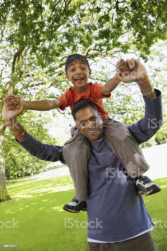 young Indian boy riding on fathers shoulders having fun outdoors stock photo