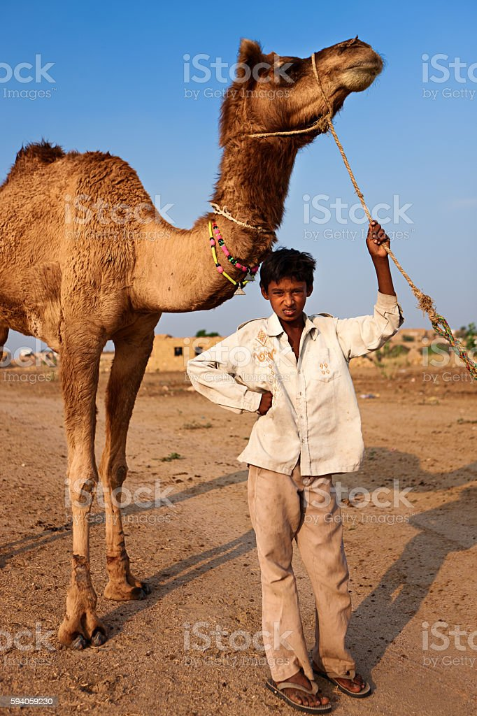 Young Indian boy with camel, Thar Desert, Rajasthan, India stock photo