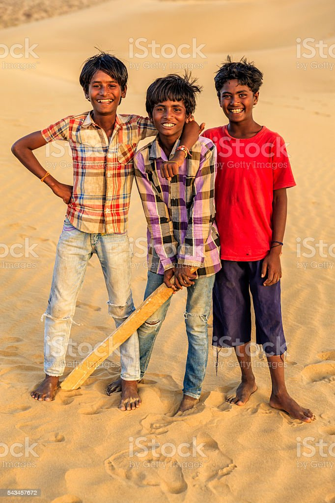 Young Indian boys playing cricket on sand dunes, India stock photo