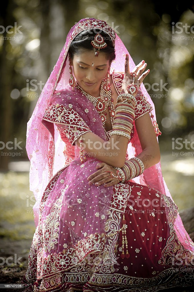 Young indian bride wearing traditional gown sitting in garden royalty-free stock photo