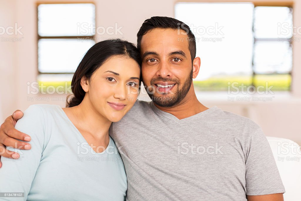 young indian couple relaxing at home stock photo