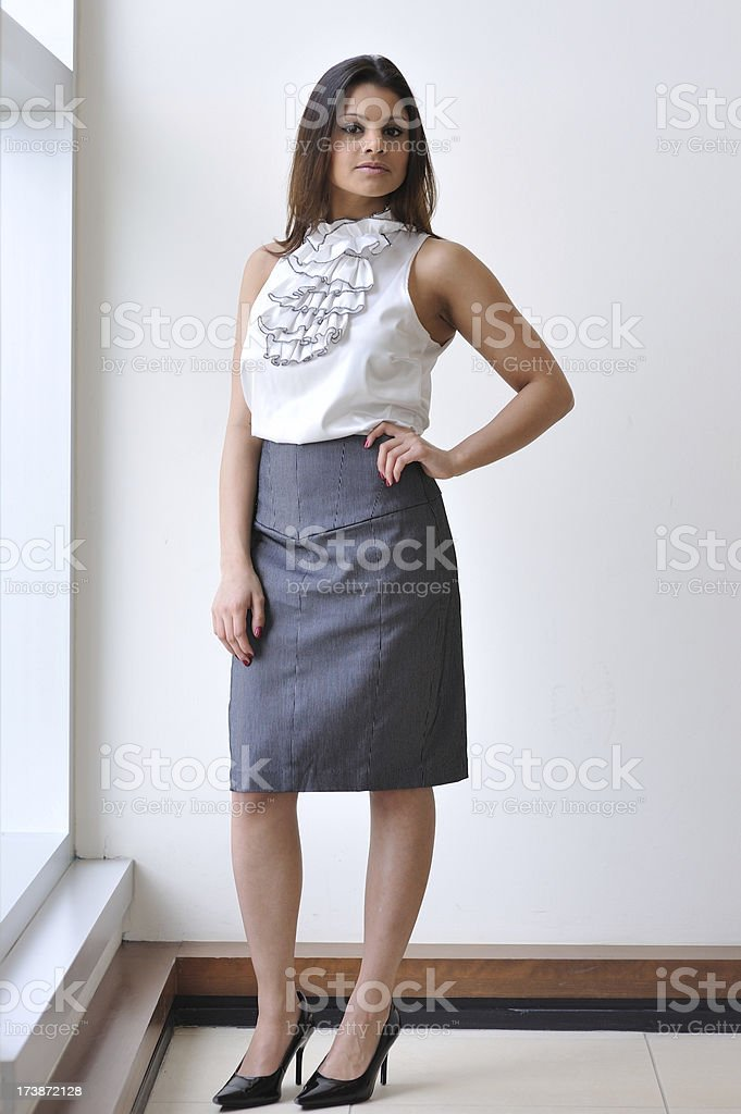 Young Indian executive standing by a window stock photo
