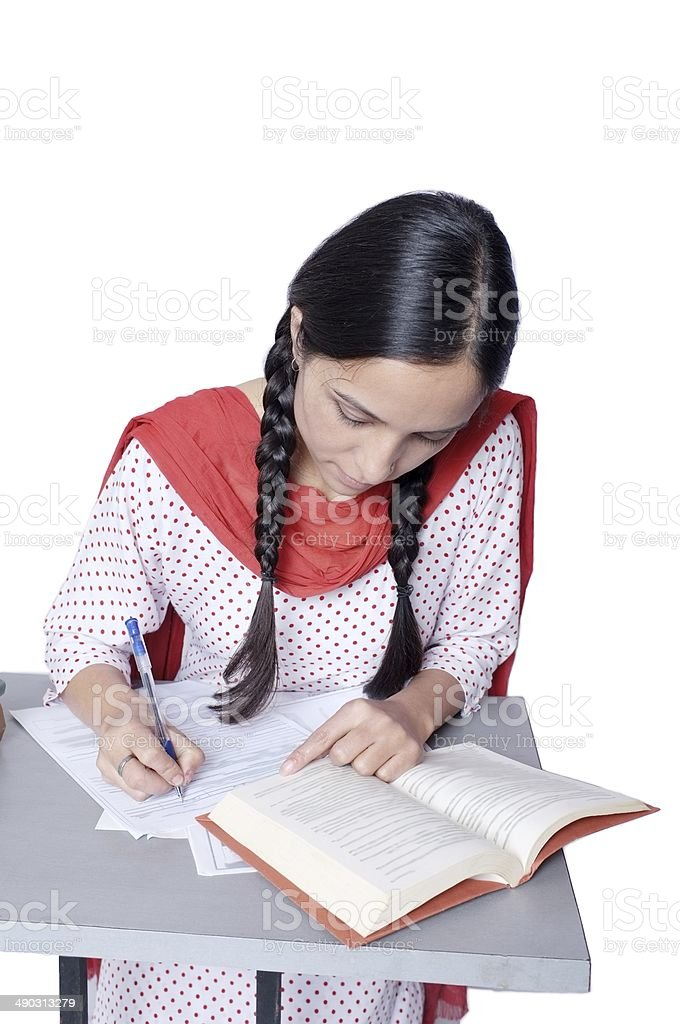 Young Indian female teenager writing in classroom. stock photo