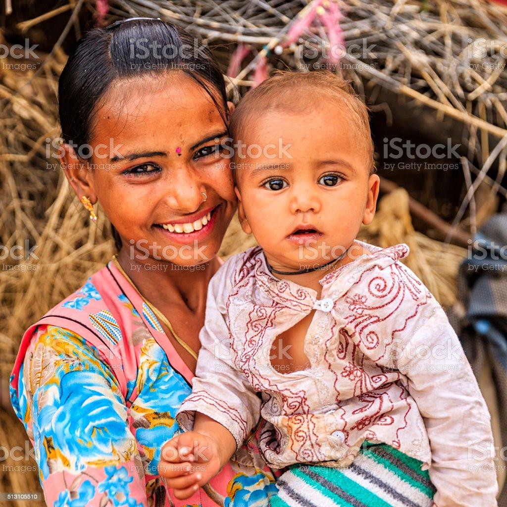 Young Indian girl holding little baby, village near Jodhpur stock photo