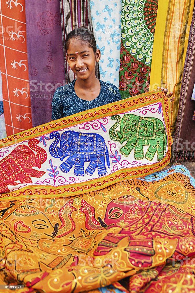Young Indian girl selling colorful embroidered rugs royalty-free stock photo