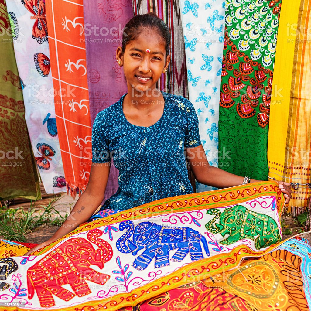 Young Indian girl selling colorful embroidered rugs stock photo
