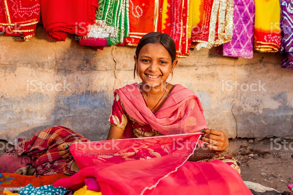 Young Indian girl selling colorful fabrics stock photo