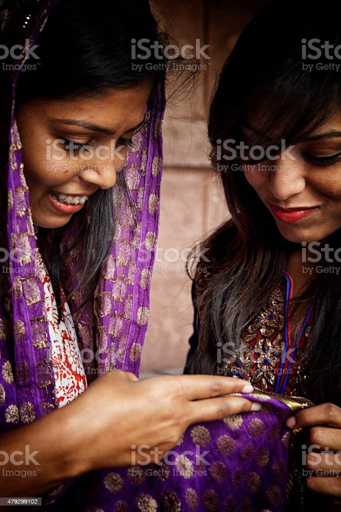 Young indian girlfriends admiring shawl. stock photo