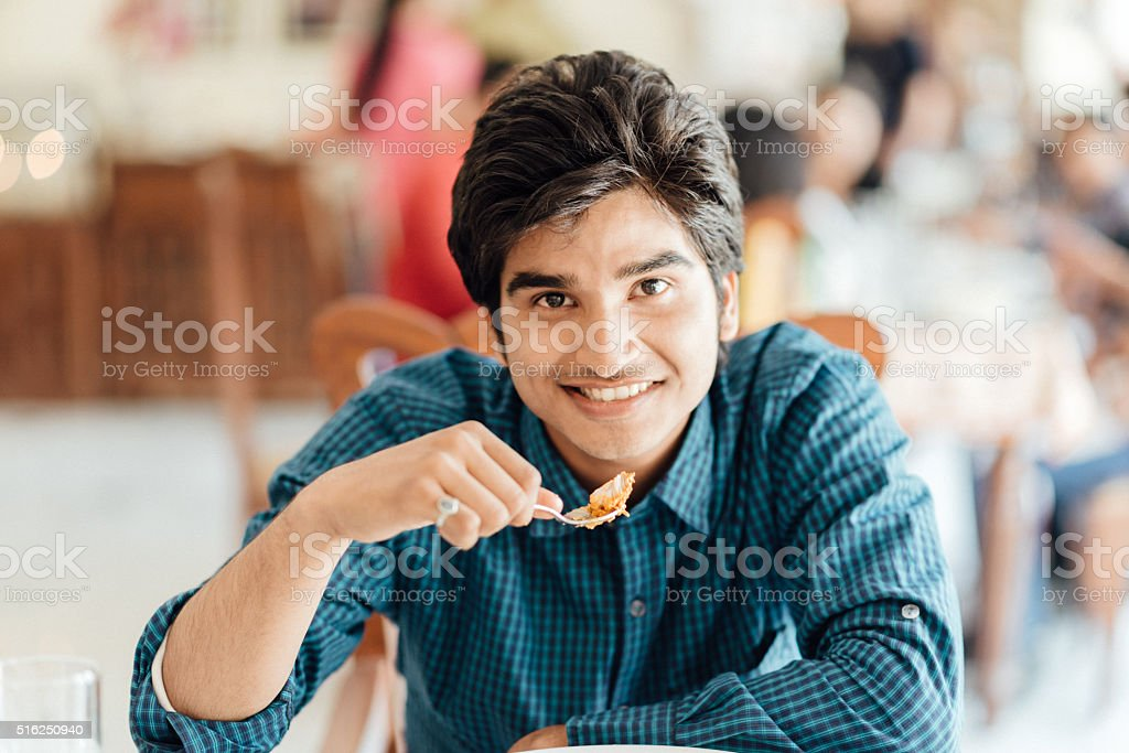 Young Indian Male eating in Restaurant stock photo