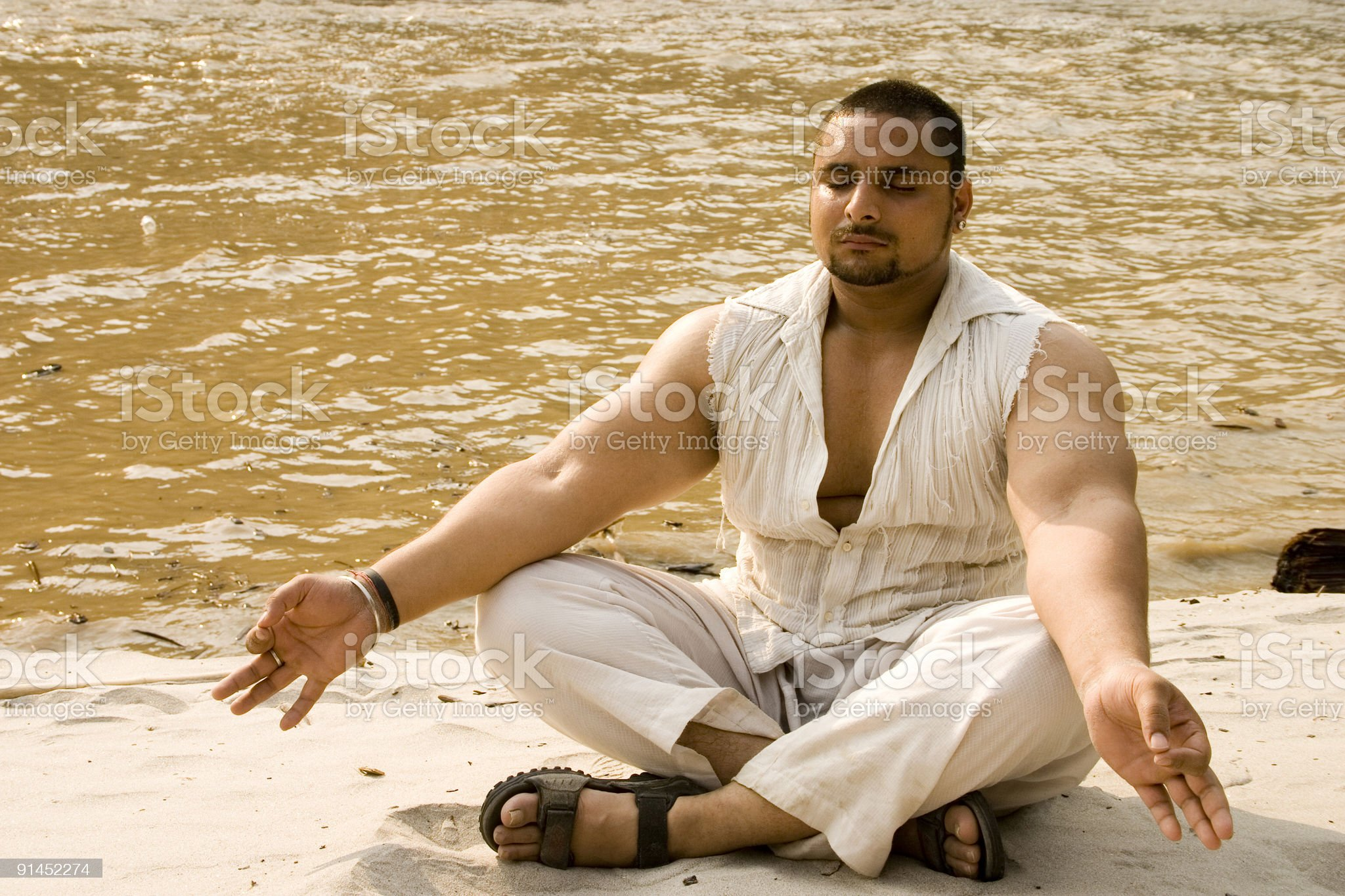 Young Indian Male yoga banks of River Ganges in Rishikesh royalty-free stock photo